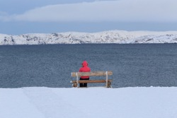 tourist sitdown on wooden chair see views from barents sea in russia , winter time