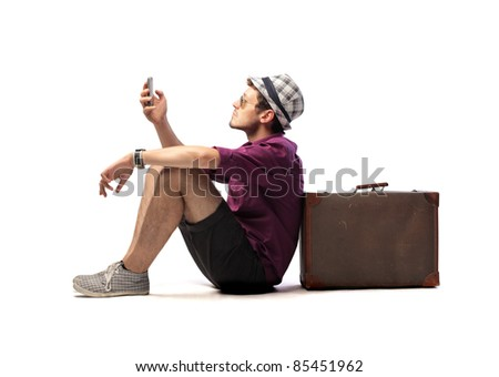 Tourist sitting against a suitcase and using a mobile phone