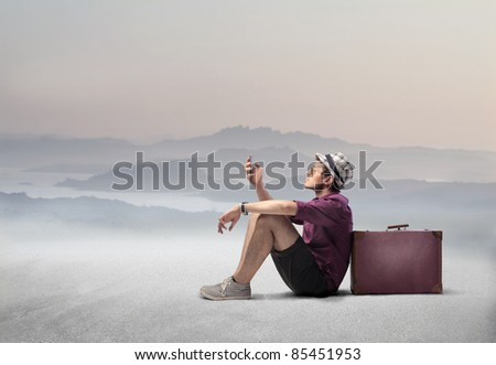 Tourist sitting against a suitcase in a desert and using a mobile phone