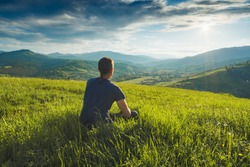 Tourist sitting on a hill in a green grass and enjoy majestic sunset above carpathian mountain valley.