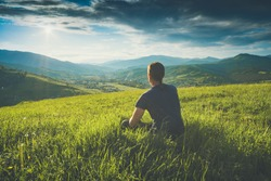 Tourist sitting on a hill in a green grass and enjoy majestic sunset above carpathian mountain valley. Instagram stylization.
