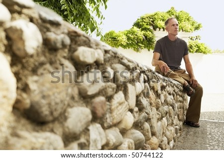 Tourist sitting on Stone Wall in Granada, Spain