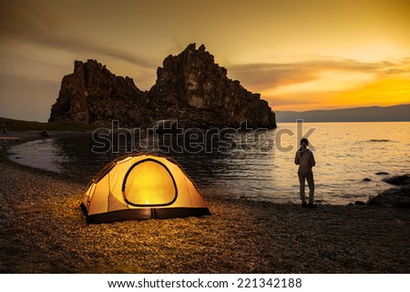 Tourist stand near tent and lake shore and looking at the beautiful sunset