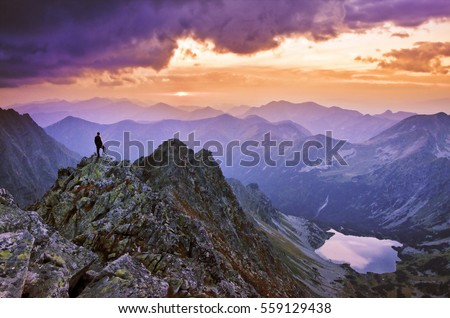 Tourist stand on the top of big mountains and looking to the valley and sky with clouds and beautiful sunset light. Wallpaper with space for your montage - aim, top, business, thinking concept photo