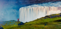Tourist standing on the shore of falling water of the most powerful waterfall in Europe - Dettifoss with raised hands. Colorful summer sunset in Jokulsargljufur National Park, Iceland.