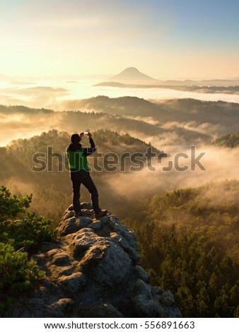 Tourist takes photos with smart phone on peak of hilly landscape. Autumn fogy hills, man photograph misty sunrise in hills and mountains.