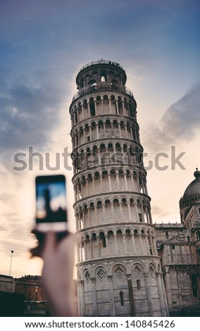 Tourist takes snapshots with smart phone digital camera of Pisa Tower at the entrance to Piazza dei Miracoli on a cold summer evening.