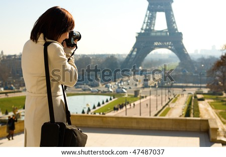 Tourist taking a picture of the Eiffel Tower in Paris