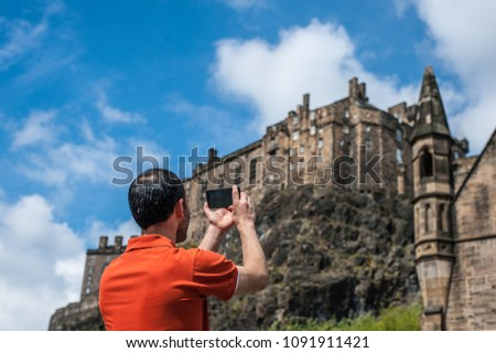 Tourist taking mobile phone pictures of Edinburgh Castle in spring time.