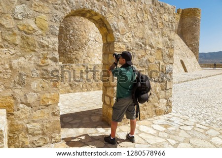 tourist taking pictures in the rampart of a castle on a sunny day
