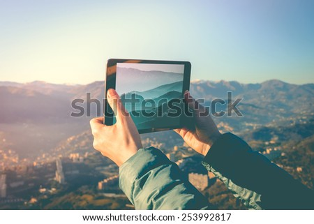 Tourist taking pictures on a tablet in mountains. Toned picture