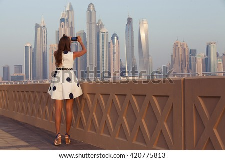 Tourist taking travel picture with phone of Dubai City skyline. Unrecognizable female young adult enjoying UAE vacations in beautiful summer dress.