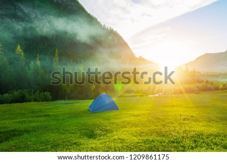 Tourist tent at the foot of the mountains. Camping on the grass near the mountain in the rays of the evening sun. Mountain landscape and sunset. #1209861175