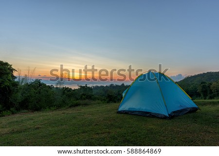 Tourist tent in camp among meadow in the mountain at sunrise #588864869