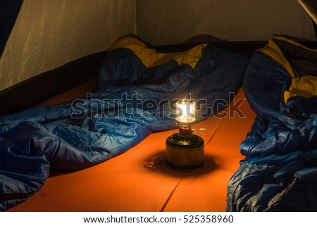 Tourist tent inside. Small Camping Tent Illuminated Inside. The gas lamp inside the tourist tents in the campaign. Tent, sleeping bags, hiking rugs and oil lamp. #525358960