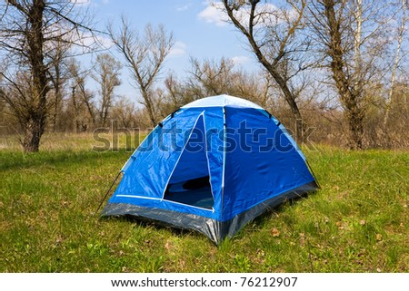 Tourist tent on green field in forest