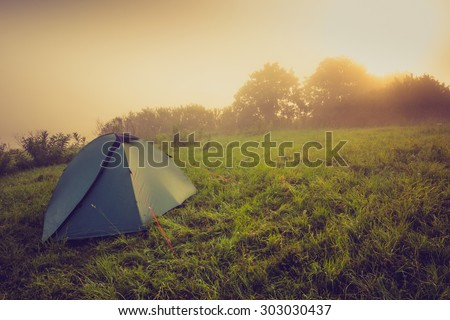 Tourist tent on green meadow at sunrise. Camping background. Freedom concept. Filtered image:cross processed vintage effect. #303030437