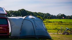 Tourist tents and car in green field at campsite. Camping place in the meadow in nature park in summer. Adventure travel active lifestyle freedom outdoors. Family time holidays.
