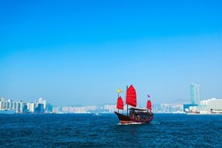 Tourist traditional style cruise sailboat with red sails crosses Victoria harbor from Kowloon to the Hong Kong Island