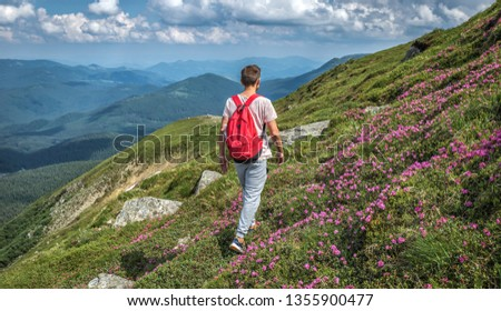 tourist traveler man makes mountain ascent trip summer with backpack. Vacations in nature rue outdoor