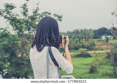 Tourist traveler photographer making pictures outdoor park on vintage photo camera on background. hipster girl enjoying peak mountain and nature holiday. Vintage retro picture style.