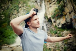 Tourist traveler with an action camera Go on his head in the background waterfall in Vietnam. concept of extreme holidays in the mountains.