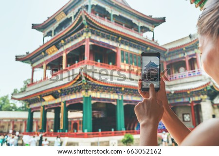Tourist using mobile phone screen for picture with smartphone of old Lama temple in Beijing, china. Asia tourism travel. People taking photos during vacation.