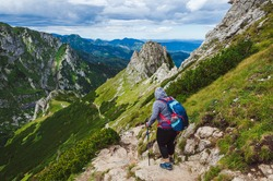 Tourist walk along picturesque hiking trail in Tatras (Carpathian Mountains, Poland). Active lifestyle and nordic walking.