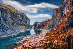 Tourist walking on the bottom of canyon with basalt columns. Unbelievable summer scene of Studlagil Canyon. Picturesque morning view of Iceland, Europe. Beauty of nature concept background.