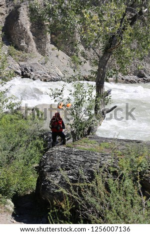 """tourist water sportsman in a diving suit against the backdrop of the threshold of the river """"turbine"""" on the river Chuya. Athlete on insurance of comrades with a rope, Altai Republic, Russia"""