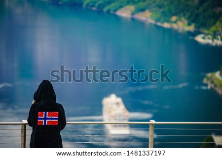 Tourist wearing norwegian flag clothing enjoying scenic view over fjord Geirangerfjorden from Flydalsjuvet viewpoint. Cruising vacation and travel. #1481337197