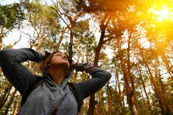 Tourist with a backpack and a hood at evergreen pine forest at sunny day. Travel, ecotourism, ecology, local tourism concept, natural background with an explorer in hoodie and coniferous trees