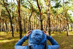 Tourist with a backpack and a hood at evergreen pine forest. Travel, ecotourism, ecology, local tourism concept, natural background with an explorer in hoodie and coniferous trees
