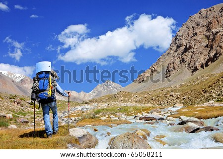 Tourist with a backpack and a mountain panorama