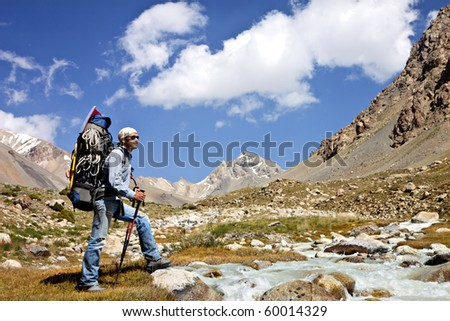 Tourist with a backpack in a mountain valley