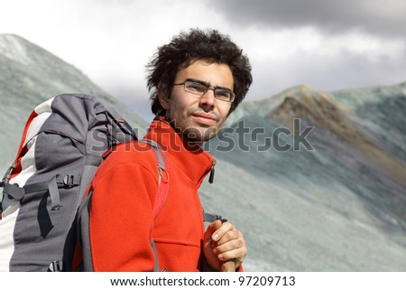 tourist with a backpack on a background of mountains