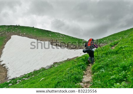 tourist with a backpack walking along the road in the mountains