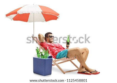 Tourist with a bottle of beer relaxing in a deck chair with an umbrella next to a cooling box isolated on white background