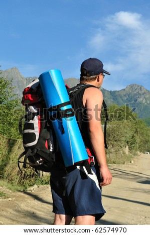 Tourist with a large backpack is a high mountain, on the road, photo from the back