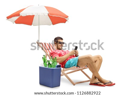 Tourist with a phone sitting in a deck chair with an umbrella next to a cooling box isolated on white background