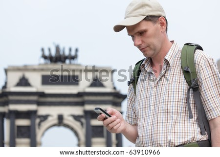 Tourist with backpack and cell phone against Triumphal arch in Moscow