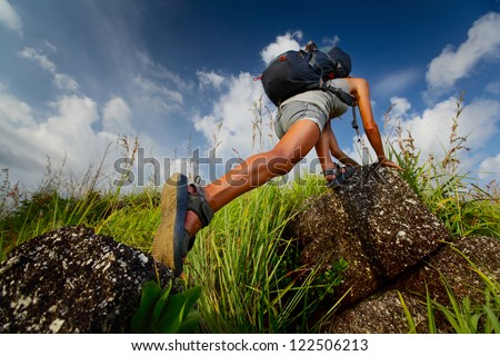 Tourist with backpack climbing a steep rock over blue sky background
