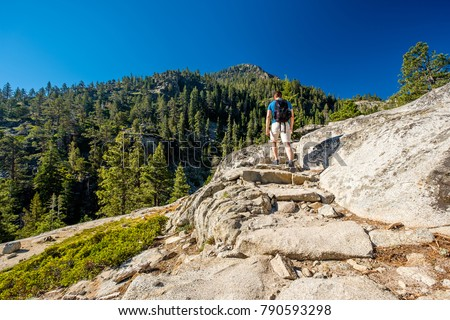 Tourist with backpack hiking in mountains at Lake Tahoe in California, USA