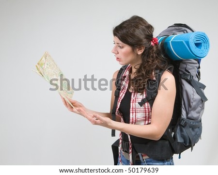 Tourist with backpack, map and compass in hands.