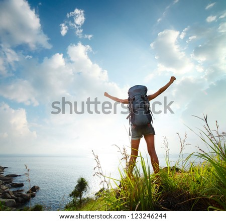Tourist with backpack standing on a rock with raised hands with sea on the background