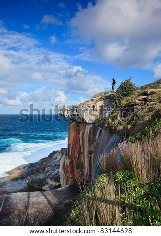 Tourist with camera standing on seaside cliff in Sydney
