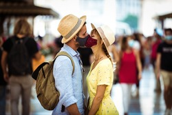 Tourist with face mask kissing in the city - New normal lifestyle concept with couple in love kiss outdoor - Tourism, love and corona virus.
