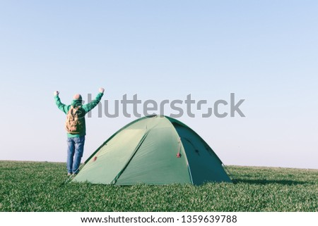 Tourist with hands up near his tent on summer field. Travel concept #1359639788
