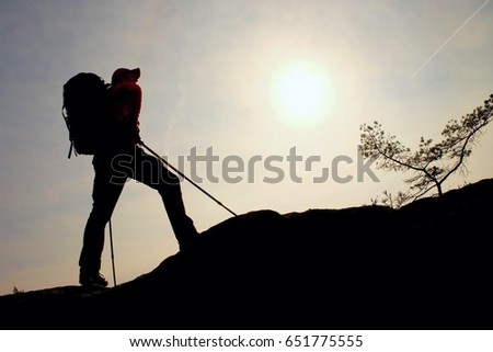 Tourist with sporty backpack and poles in hands stand on rock  watching up to hill for next step. Sunny spring daybreak in mountains. Vivid and strong vignetting effect..  #651775555