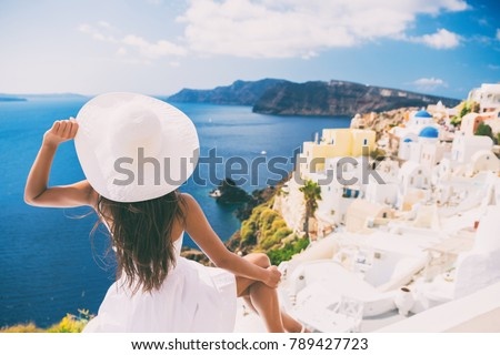 Tourist woman at view of Santorini cruise travel. Beautiful white village of Oia with Caldera and mediterranean sea. Girl in sun hat and red dress enjoying summer travel vacation in Europe.